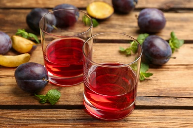 Delicious plum liquor, mint and ripe fruits on wooden table. Homemade strong alcoholic beverage