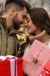 Lovely couple with Christmas presents near festively decorated store outdoors