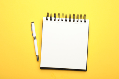 Stylish open notebook and pen on yellow background, top view