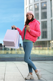 Beautiful young woman with cup of coffee and shopping bags near building