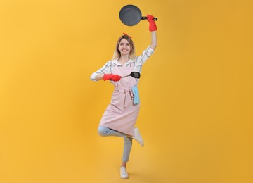 Young housewife meditating with frying pan and spatula on yellow background