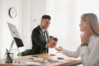 Man giving cup of coffee to his colleague in office. Flirting at work