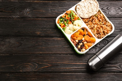 Thermos bottle and lunch box with food on black wooden background, flat lay. Space for text