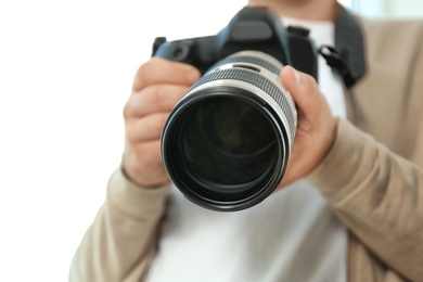 Male photographer with professional camera on white background, closeup