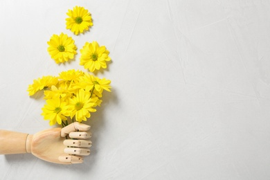 Wooden mannequin hand and yellow flowers on white background, flat lay. Space for text