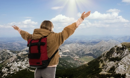 Tourist with travel backpack enjoying mountain landscape during vacation trip