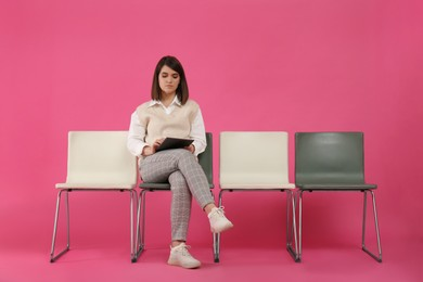 Young woman with tablet waiting for job interview on pink background