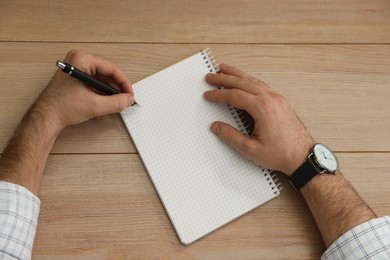 Left-handed man writing in notebook at wooden table, top view
