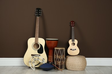 Set of different string and percussion musical instruments near brown wall indoors