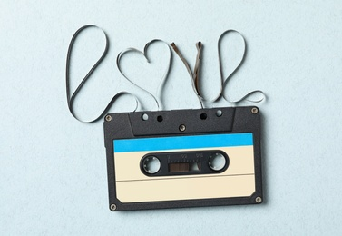 Music cassette and word Love made with tape on turquoise background, top view. Romantic song