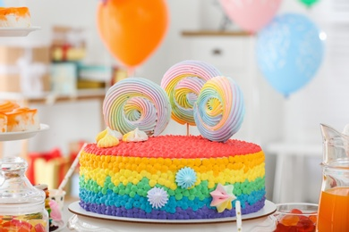 Bright birthday cake and other treats on table in decorated room