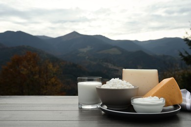 Tasty cottage cheese and other fresh dairy products on grey wooden table in mountains. Space for text