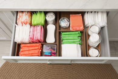 Storage of different feminine hygiene products in drawer indoors, top view