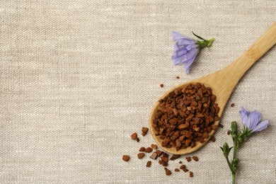 Spoon of chicory granules and flowers on sackcloth, flat lay. Space for text