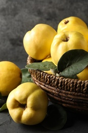 Fresh ripe organic quinces with leaves in wicker basket on table, closeup