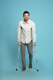 Full length portrait of man with crutches on light blue background