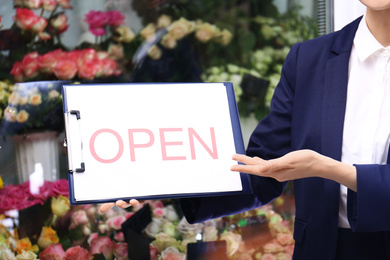 Female business owner holding OPEN sign near flower shop, closeup