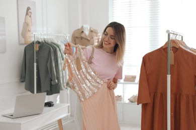 Young woman choosing clothes near rack in modern boutique