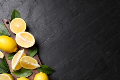 Many fresh ripe lemons with green leaves on black table, top view. Space for text