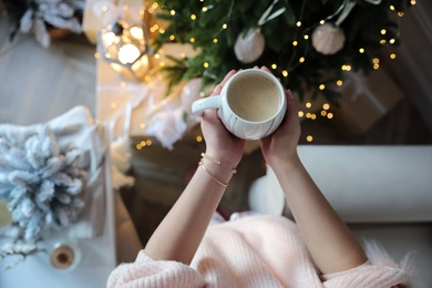 Woman with cup of cocoa in room decorated for Christmas, above view