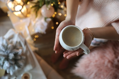 Woman with cup of cocoa in room decorated for Christmas, top view