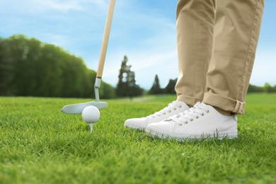 Person playing golf on green course, closeup