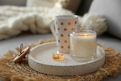 Cup of drink and burning candles on sofa in room. Interior elements