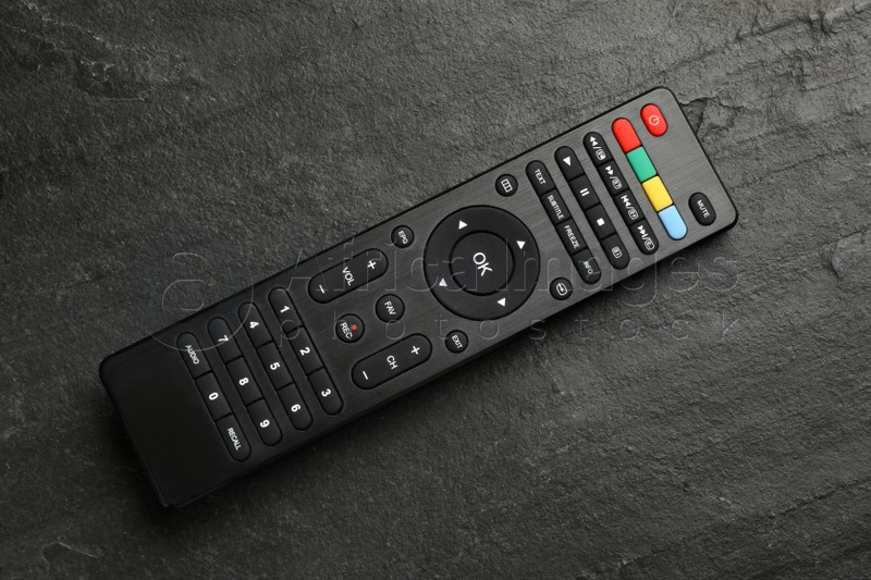 Modern tv remote control on black table, top view