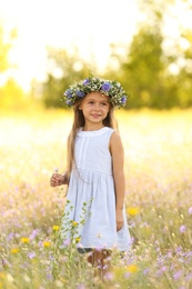 Cute little girl wearing flower wreath outdoors. Child spending time in nature