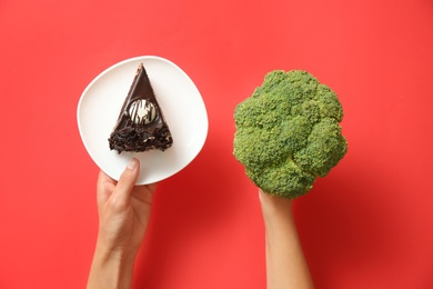 Top view of woman choosing between cake and healthy broccoli on red background, closeup