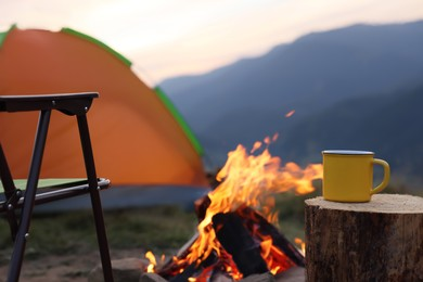 Yellow mug with hot drink on wooden stump near bonfire outdoors, space for text. Camping season