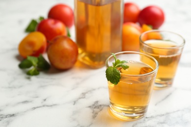 Delicious plum liquor with mint on white table. Homemade strong alcoholic beverage