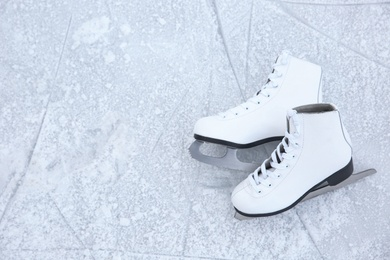 Pair of figure skates on ice, top view with space for text. Winter outdoors activities