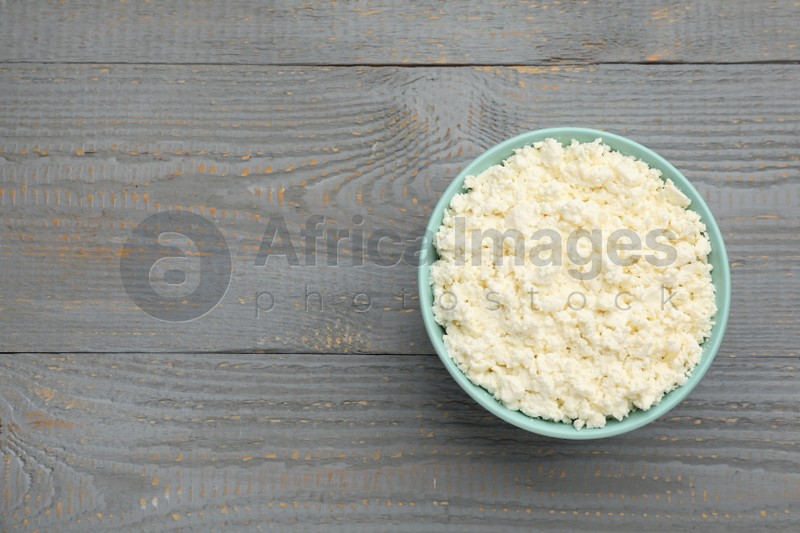 Delicious fresh cottage cheese on grey wooden table, top view. Space for text