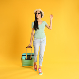 Beautiful woman with suitcase for summer trip on yellow background. Vacation travel