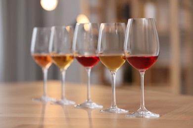 Different sorts of wine in glasses prepared for tasting on wooden table indoors