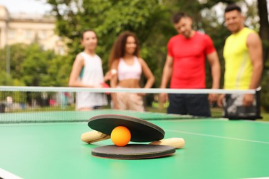 Friends talking near ping pong table outdoors, focus on rackets and ball