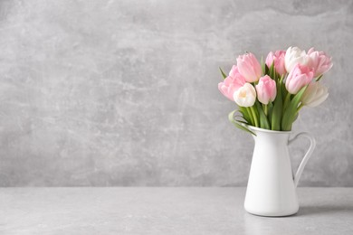 Beautiful bouquet of tulips in jug on light table. Space for text
