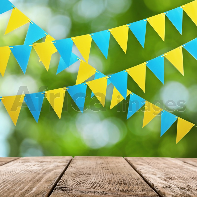 Empty wooden table and decorative bunting flags outdoors