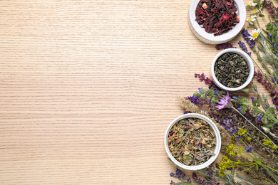 Flat lay composition with healing herbs on wooden table. Space for text