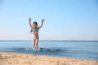 Cute little child having fun in sea on sunny day. Beach holiday