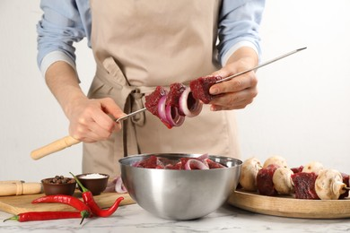 Woman stringing marinated meat on skewer at white marble table, closeup