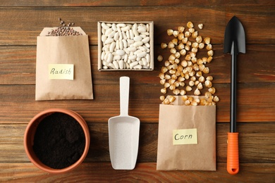 Vegetable seeds, pot and gardening tools on wooden table, flat lay