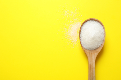 Granulated sugar in spoon on yellow background,top view. Space for text