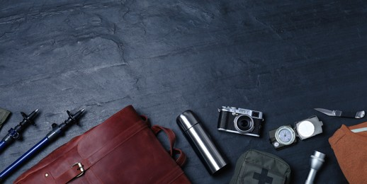 Flat lay composition with leather tourist backpack and camping equipment on black background, space for text