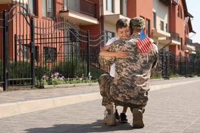 Soldier and his little son with flag of USA hugging outdoors