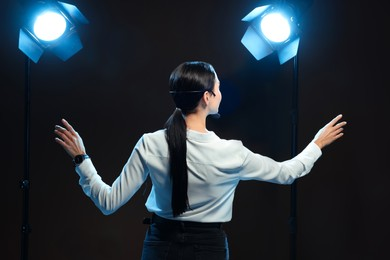 Motivational speaker with headset performing on stage, back view