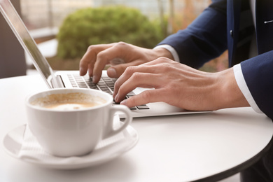 Businessman working with laptop in outdoor cafe, closeup. Corporate blog