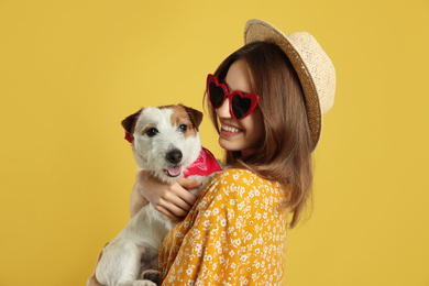 Young woman with her cute Jack Russell Terrier on yellow background. Lovely pet