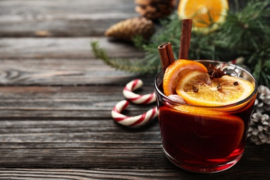 Glass cup of tasty mulled wine on black wooden table. Space for text